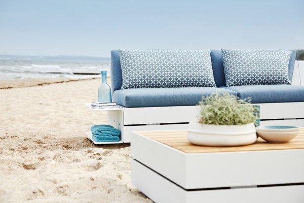 Lounge mit Tisch in weißem Holz und mit blauen Kissen
