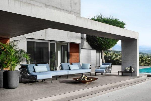 elegante Lounge mit hellblauer Polsterung und mit moderner Feuerschale