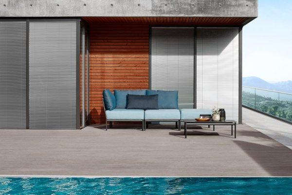 Schlichte Graue Lounge mit viereckigem Tisch und hellblauen Polstern