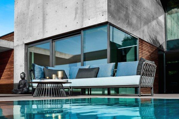 graue Lounge in modernem Stil mit türkisfarbenen Kissen und mit Beistelltisch